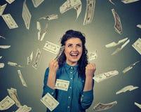 La donna esulta i pugni di pompaggio estatici celebra il successo sotto la pioggia dei soldi che cade banconote delle banconote i Immagini Stock Libere da Diritti