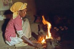 La donna etiopica sta cucinando su un fuoco di legno Immagine Stock