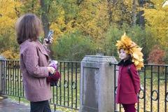 La donna fa la foto della ragazza sveglia in una corona delle foglie di acero gialle fotografie stock libere da diritti