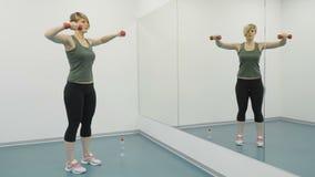 La donna fa gli esercizi per i suoi bicipiti nella palestra video d archivio