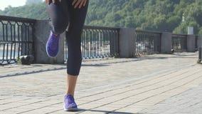 La donna fa gli esercizi per le gambe sul riverwalk stock footage