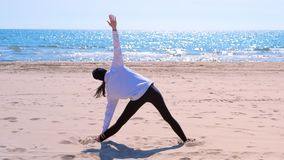 La donna fa l'esercizio di sport della spiaggia del mare della sabbia di posa di yoga del triangolo per la vista posteriore adatt stock footage