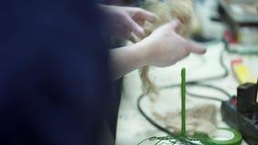La donna fa la base per la disposizione floreale dentro il negozio della decorazione del fiore archivi video