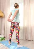 La donna fa la forma fisica che allunga a casa su una stuoia blu nel colpo della parte posteriore del salone Fotografia Stock