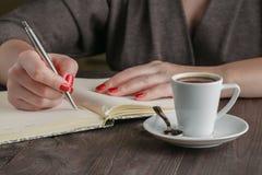 La donna fa la pianificazione e beve il caffè Fotografie Stock Libere da Diritti