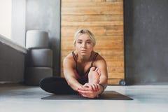 La donna fa la posa di yoga nella classe, si siede il asana di andata della curvatura Fotografie Stock Libere da Diritti