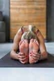 La donna fa la posa di yoga nella classe, si siede il asana di andata della curvatura Immagini Stock