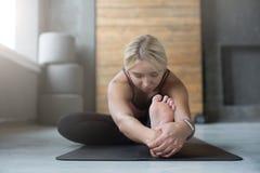 La donna fa la posa di yoga nella classe, si siede il asana di andata della curvatura Fotografia Stock
