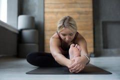 La donna fa la posa di yoga nella classe, si siede il asana di andata della curvatura Immagine Stock Libera da Diritti