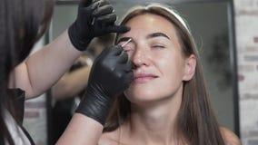 La donna fa le sopracciglia luminose con il salone di bellezza video d archivio