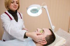 La donna fa la maschera del cetriolo per il paziente fotografie stock