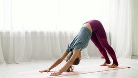 La donna fa la posa orientata verso il basso del cane allo studio di yoga archivi video