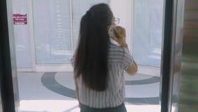 La donna fa la telefonata dentro un elevatore stock footage