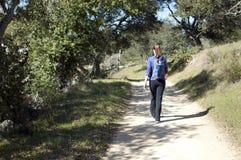 La donna fa un'escursione su il fireroad della sporcizia, a partire dalla macchina fotografica, spazio vuoto lasciato Fotografia Stock