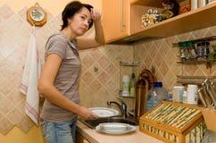 La donna faticosa lava gli articoli per la tavola Immagini Stock