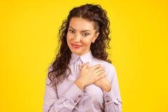 La donna fedele tiene le mani sul petto vicino a cuore, le mostra la gentilezza fotografia stock