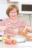La donna felice aggiunge lo zucchero in una ciotola fotografie stock