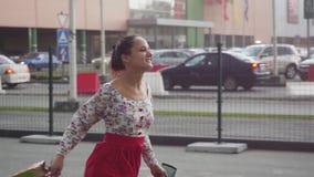 La donna felice castana giovane in bello vestito con i sacchetti della spesa va sulla via al rallentatore 1920x1080 archivi video