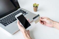 La donna felice che per mezzo dello Smart Phone e la carta di credito registrano i pagamenti Immagine Stock Libera da Diritti
