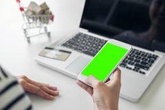 La donna felice che per mezzo dello Smart Phone e la carta di credito registrano i pagamenti Immagini Stock