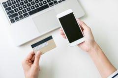 La donna felice che per mezzo dello Smart Phone e la carta di credito registrano i pagamenti Fotografia Stock