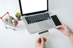 La donna felice che per mezzo dello Smart Phone e la carta di credito registrano i pagamenti Immagine Stock