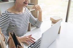 La donna felice che per mezzo dello Smart Phone e la carta di credito registrano i pagamenti Fotografia Stock Libera da Diritti