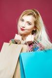 La donna felice che porta la camicia luminosa sta tenendo molte borse variopinte di acquisto Bionda stupefacente con i capelli ed fotografia stock libera da diritti