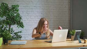 La donna felice che ritiene eccitata esaminando lo schermo del computer portatile che si siede nel luogo di lavoro, celebra il su video d archivio