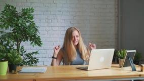 La donna felice che ritiene eccitata esaminando lo schermo del computer portatile che si siede nel luogo di lavoro, celebra il su archivi video
