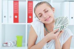 La donna felice che tiene i dollari in mani e vuole spendere i soldi Fotografie Stock
