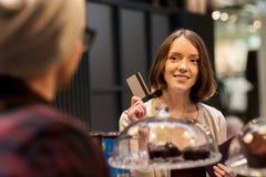 La donna felice con acquisto della carta di credito agglutina al caffè Immagini Stock Libere da Diritti