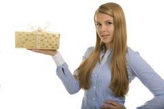 La donna felice con i panni caldi presenta un regalo di Natale dorato Fotografia Stock