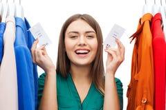 La donna felice con la vendita etichetta sui vestiti al guardaroba Immagini Stock
