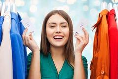 La donna felice con la vendita etichetta sui vestiti al guardaroba Immagini Stock Libere da Diritti