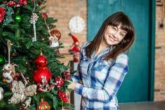 La donna felice decora un albero di Natale nella stanza Concetto di Fotografia Stock