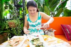La donna felice del asean gode di di mangiare nel giardino Fotografia Stock Libera da Diritti