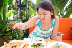 La donna felice del asean gode di di mangiare nel giardino Immagine Stock