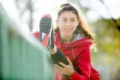 La donna felice del corridore che fa l'allungamento si esercita sul ponte Immagine Stock