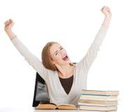 La donna felice dello studente con le sue mani aumenta e pila di libri. Immagine Stock Libera da Diritti
