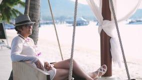 La donna felice dentro è invecchiato in cappello ed occhiali da sole che riposano su un'oscillazione di legno su una spiaggia tro archivi video