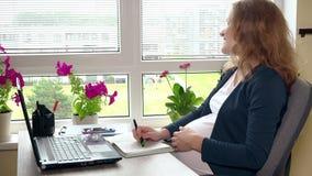 La donna felice di affari che guardano attraverso la finestra e la carezza segnano la sua grande pancia video d archivio