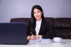 La donna felice di affari che lavora con il computer portatile e scrive J Fotografia Stock Libera da Diritti