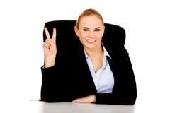 La donna felice di affari che si siedono dietro lo scrittorio e la vittoria di manifestazioni firmano Fotografie Stock Libere da Diritti