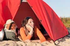 La donna felice di campeggio si distende la tenda sulla spiaggia immagini stock