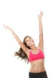 La donna felice di forma fisica con le braccia ha sollevato lo sguardo in su Fotografia Stock Libera da Diritti