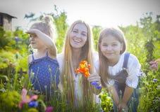 La donna felice e le sue figlie nella molla di fioritura fanno il giardinaggio fotografia stock libera da diritti
