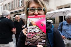 La donna felice esibisce un opuscolo turistico della città di strasbour immagini stock libere da diritti