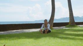 La donna felice fa la pratica ed il tratto di yoga giù in avanti alle gambe sulla spiaggia dell'oceano, sui bei precedenti e sui  stock footage