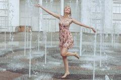 La donna felice gioca rumorosamente in una fontana Immagini Stock Libere da Diritti